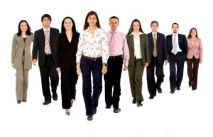 Business team walking forward - leadership and teamwork concepts using a group of businessmen and businesswomen isolated over a white background